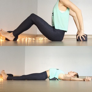 Gently roll to one side and then come back to seated. Now, position the block horizontally where it will be positioned into the middle of the back. Your hips should touch the ground.